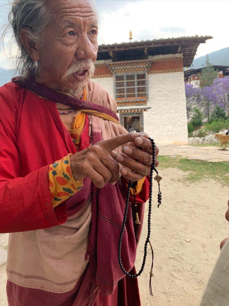 A Milarepa Nakpa yogi teaches Heather Elton proper mala technique.