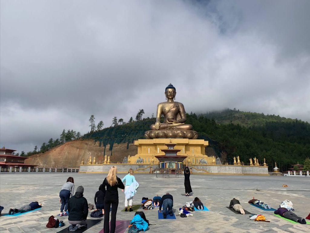 Students on the Elton Yoga Bhutan Yoga Adventure doing prostrations before the Buddha Dordenma.